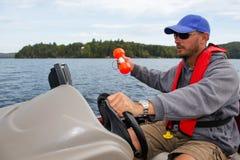 在小船标志浮体和生波探侧器的人渔 图库摄影