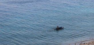 在小船的人航行 免版税库存图片