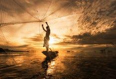 在小船的剪影渔夫捕鱼网 泰国 免版税库存照片