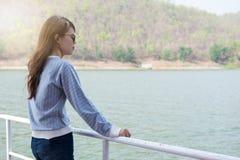 在小船的少妇常设观察风景 前面她有 免版税库存照片