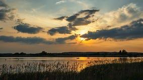 在小船的日落在河 免版税库存图片