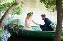 在小船的浪漫爱情小说 有花圈和白色礼服的妇女 欧洲传统 免版税图库摄影