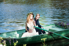 在小船的浪漫爱情小说 有花圈和白色礼服的妇女 欧洲传统 库存图片