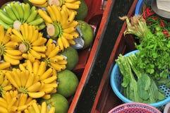 在小船的热带水果和蔬菜产品卖的在Damnoen Saduak浮动市场上 免版税库存照片