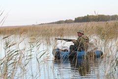 在小船的猎人 免版税库存照片