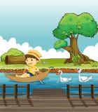 在小船的男孩骑马被鸭子跟随了 免版税库存照片