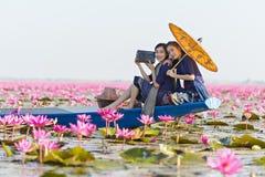 在小船的老挝妇女听的收音机在花莲花湖,佩带传统泰国人,红色莲花海UdonThani泰国的妇女 免版税图库摄影
