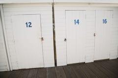 在小船的被绘的白色木存贮门靠码头 免版税库存照片