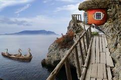 在小船的鸟从海回到在家他们的岩石的苹果房子 免版税库存图片