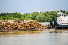 在小船运输的许多木日志由水 库存照片