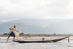在小船onLake的渔夫展开捕鱼网 库存图片