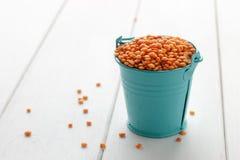 在小蓝色桶的干红色小扁豆在白色木背景 图库摄影