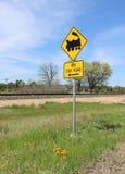 在小路标志的黑和黄色火车在铁路轨道附近 库存图片