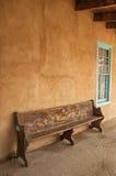 在小野鸭被整理的窗口旁边的木长凳 免版税库存图片