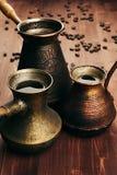 在小组破旧的古色古香的土耳其罐cezve的热的咖啡与crema,与迷离的豆在棕色老木板背景,垂直的s 库存图片