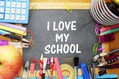 在小黑板的学校用品充满i爱我的学校词 免版税库存图片