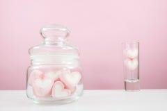 在小玻璃瓶子的可爱的桃红色心脏蛋白软糖 免版税库存照片