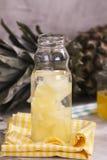 在小玻璃瓶的菠萝饮料 免版税图库摄影