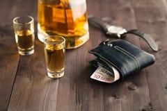 在小玻璃的倾吐的酒精 免版税库存照片