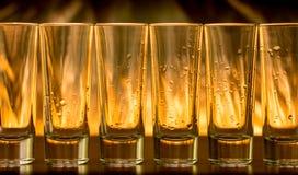 在小玻璃的灼烧的鸡尾酒在桌上 免版税库存图片