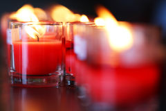 在小玻璃的特写镜头红色祷告蜡烛在天主教会里 免版税库存照片