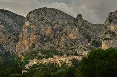 在小Provencal镇Moustiers Sainte玛里上的巨型的岩石 库存照片