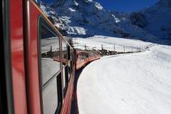 在少女峰,瑞士训练移动在积雪的山下 免版税库存照片