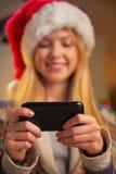 在少年女孩的特写镜头圣诞老人帽子文字sms的 免版税库存图片