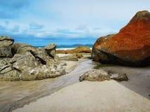 在尖叫的海滩的红色石头 免版税库存照片