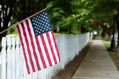 在尖桩篱栅的美国国旗 库存照片