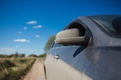 在尘土的汽车侧视图和在地面路的blured夏天领域 免版税库存图片