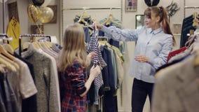 在尝试在T恤杉的服装店和他们中的一个的妇女年轻俏丽的夫妇寻找新的衣裳中 股票视频