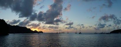 在尤宁岛的日落有帆船游艇的在圣文森特和格林纳丁斯,加勒比附近的多巴哥岩礁 图库摄影