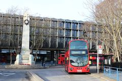 在尤斯顿驻地的红色伦敦公共汽车由战争纪念建筑 免版税库存图片