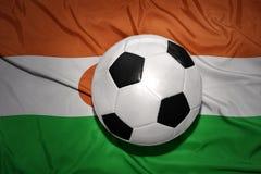 在尼日尔的国旗的黑白橄榄球球 库存图片