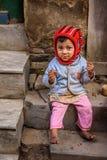 在尼泊尔吃在加德满都街道的一个可怜的女孩一个薄脆饼干  免版税库存照片