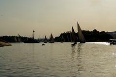 在尼罗河的日落的由后面照的照片在开罗附近的有尼罗河的典型的帆船的剪影的叫 免版税库存图片