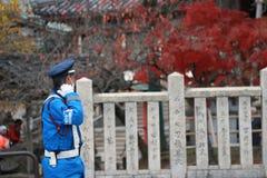 在尽在街道上的蓝色制服的日本交通警旁边职责 免版税库存照片