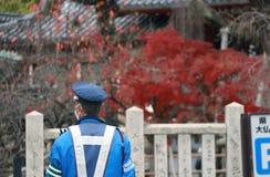 在尽在街道上的蓝色制服的日本交通警职责与背景红色树在秋天 免版税库存图片