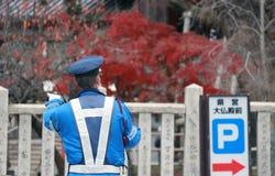 在尽在街道上的蓝色制服的日本交通警职责与背景红色树在秋天 图库摄影