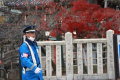 在尽在街道上的蓝色制服的日本交通警职责 库存图片
