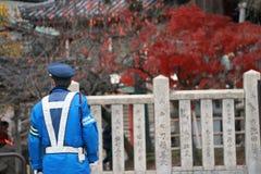 在尽在街道上的蓝色制服的日本交通警职责 免版税库存图片