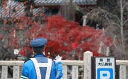 在尽在街道上的蓝色制服的日本交通警职责 库存照片