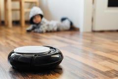 在层压制品的地板上的机器人吸尘器 免版税库存照片
