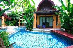 在屋子的游泳池,在庭院旁边的太阳懒人和平房 免版税库存图片