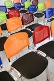 在屋子里安排的多色的椅子 免版税库存照片