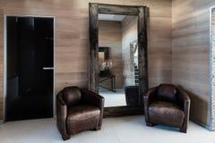 在屋子里是古色古香的镜子和椅子 免版税图库摄影