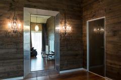 在屋子里是葡萄酒镜子和古董黄铜水晶轻的墙壁灯台 免版税库存图片