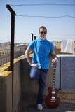 在屋顶大阳台的年轻音乐家画象 图库摄影