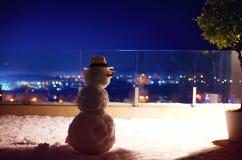 在屋顶大阳台,城市背景的逗人喜爱的雪人 库存照片